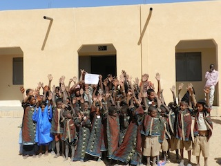 Group of happy students outside their new school in Mali