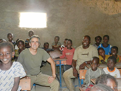 Image of Caravan to Class founder and director Barry Hoffner in one of the organization-funded classrooms with students