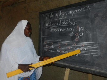 Image of an adult woman participating in the female adult education program at a Caravan To Class school in Mali