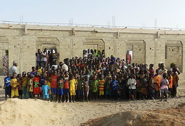 Image of villagers and construction crew while work proceeds at the school in Kakondji