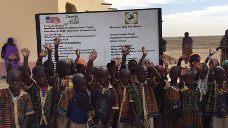 Image of the dedication plaque with students from the school in the village of Kakondji built by Caravan to Class