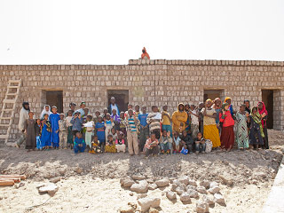 Village people from Mora stand in front of the school being constructed by Caravan to Class